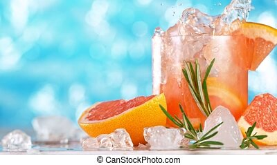 Super slow motion. Ice cube falling into glass of grapefruit gin cocktail or home made lemonade with sea surface background.