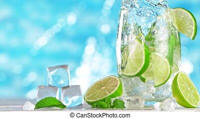 Super slow motion. Ice cube falling into glass of mojito cocktail with sea surface background.