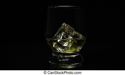 Super slow motion icy in a glass of whiskey