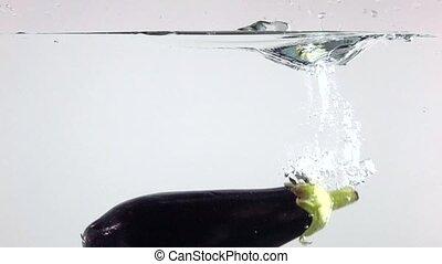 Super slow motion of eggplant falling down in water, white background