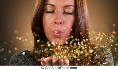 Sexy brunette woman with blowing gold glitters towards the ...