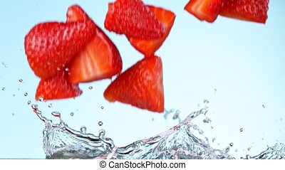 Super slow motion of strawberries falling into cream.