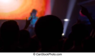 Super slow motion: people crowd silhouettes partying, cheering and raising hands up at rock concert in front of stage of nightclub. Bright colorful stage lighting. Nightlife and entertainment concept