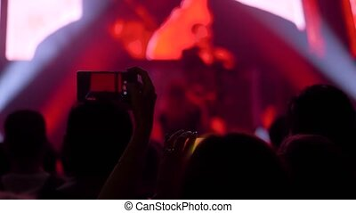 Super slow motion: people recording video of live music concert with smartphone