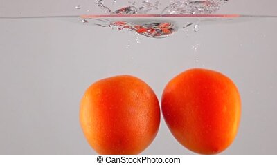 Super slow motion: red ripe tomatoes fall and float in water, gray background