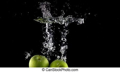 Super slow motion shot: falling juicy green apples and splashes of water