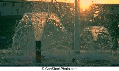 Super slow motion shot of a beautiful park fountain against sunset, orange sun, 240 fps