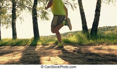 Super slow motion shot of a sportsman running along the park alley