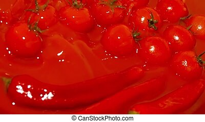 Super slow motion shot of a tomato falling down in red spicy...