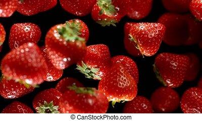 Super Slow Motion Shot of Flying Fresh Strawberries on Black Background at 1000fps.