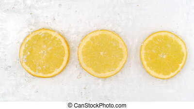 Super Slow Motion Shot of Splashing Water to three orange Slices view from above.