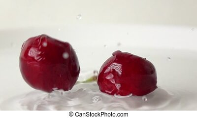 Super slow motion shot of two cherries with same stem hitting wet white plate
