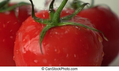 Super slow motion shot of water splashes on red ripe tomato with green leaves