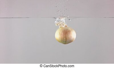 Super slow motion shot of whole onion falling into water, gray background