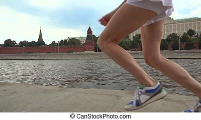 Super slow motion steadicam shot of athletic brunette girl runner against Moscow Kremlin 240 fps