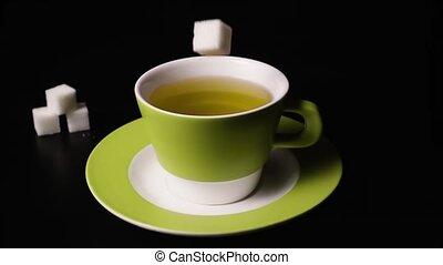 Super slow motion sugar cubes falling into tea