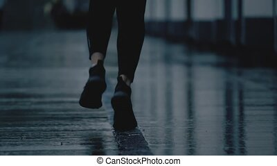 Super slow motion telephoto shot of young woman's feet running on wet pavement after rain