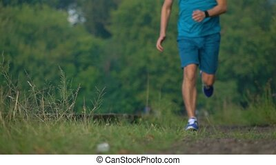 Super slow motion telephoto video of athletic man running towards the camera, 240 fps