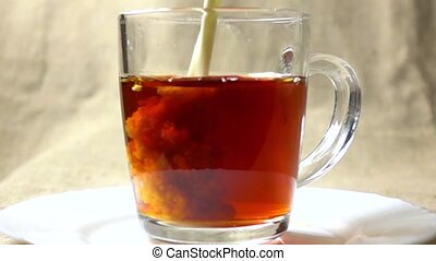 Super slow motion video of adding milk to black tea in a glass mug