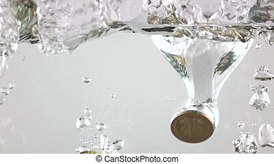 Super slow motion video of euro coins sinking in water. Crisis concept