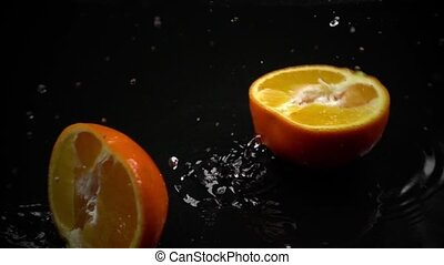 Super slow motion video of falling and splitting orange clip