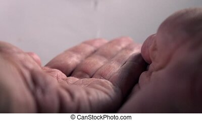 Super slow motion video of man's hands being washed