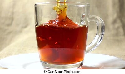 Super slow motion video of two sugar cubes falling into glass cup of black tea