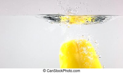Super slow motion video of yellow bell pepper falling down in water