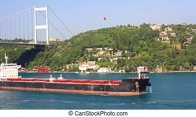 Super tanker with full of load sailing under the bridge. Extra large cargo ship sailing in to Bosphorus by letting out a very loud horn noise. A 229 mt long, 32 mt width vessel, has a deadweight of 80,459 tons