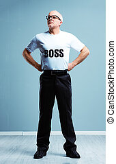 Supercilious haughty Boss stereotype with a studio shot of a senior man wearing a Boss T-shirt standing with hands on hips look up and off to the side