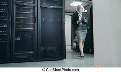 Blond woman approaching camera to inspect supercomputer work