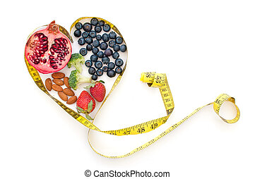 Superfoods such as pomegranate, blueberries and almonds inside a tape measure in the shape of a heart