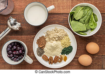 ingredients of healthy breakfast smoothie: almond milk, raw eggs, fresh spinach, frozen blueberries, whey protein, cacao, chiai seeds, pecan nuts, maca root powder, spirulina, spices (cinnamon, ginger, turmeric) with a stick blender on a rustic table