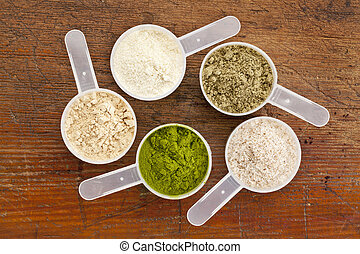superfood supplement powder - five plastic measuring cups of...