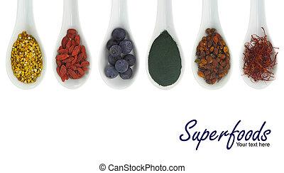 Superfoods in porcelain spoons. Pollen, goji berries,...