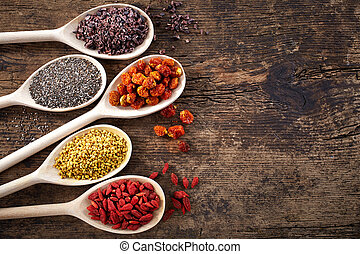 Wooden spoons of various superfoods on old wooden background
