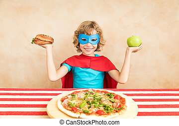 Superhero child eating superfood