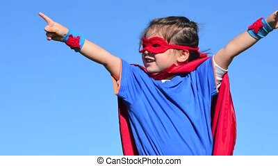Superhero girl child play pretrent outdoors with her mother