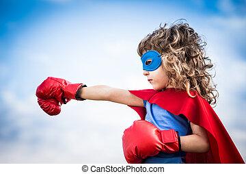 Superhero kid against dramatic blue sky background