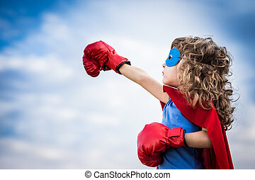 Superhero kid against summer sky background. Girl power and feminism concept