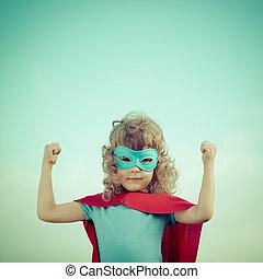 Superhero kid against summer sky background. Girl power and...