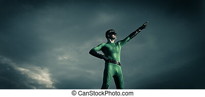 Superhero pointing with dramatic background