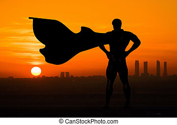 Superhero silhouette back view over watching the city at sunset or sunrise for security and defense the city from crime and illegal activities