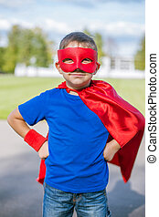 Boy dressed in cape and mask standing with hands on hips