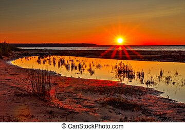 Incredible sunset on a remote beach over the great waters of Lake Superior; the largest freshwater lake in the world. Upper Peninsula, Michigan.