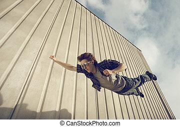 Superman - A young man feels like a superhero, flying free.