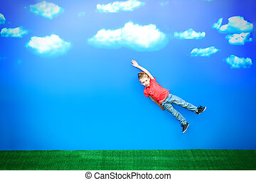 superman - Happy boy flying in a blue sky in a bright summer...