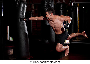 Fearles MMA Fighter practicing his superman punch on a punching bat at a gym