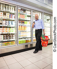Supermarket Cell Phone - Mature man looking at mobile phone...