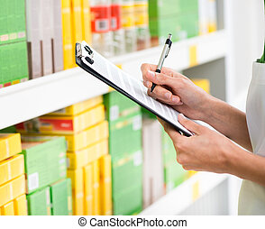Supermarket clerk at work holding pen and clipboard with...